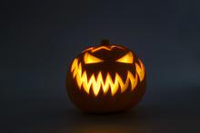 Bright Orange Jack-o'-lantern Pumpkin On Dark Solid Background. Glowing Eyes And A Terrible Grin. Halloween Minimal Concept. Copy Space. Desktop Wallpapers