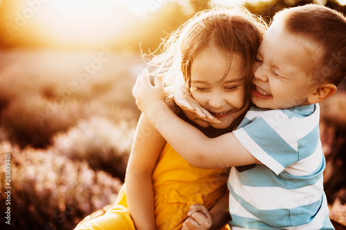 Tableau sur Toile Close up portrait of a little brother and sister embracing with eyes closed laughing against sunset in a lavender field