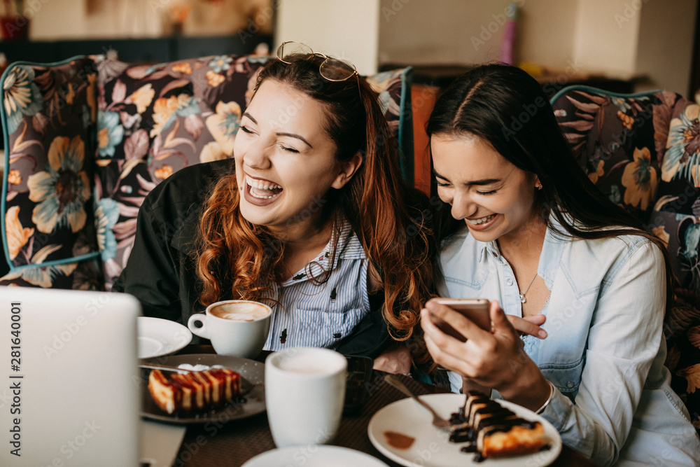Fototapety, obrazy: Two girlfriend having fun laughing while sitting in a cafe .