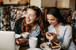 canvas print picture - Two girlfriend having fun laughing while sitting in a cafe .