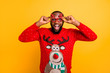 Portrait of his he nice attractive stylish cheerful cheery glad funky guy wearing cool winter Santa look outfit style touching specs isolated over bright vivid shine yellow background