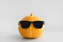 Juicy Bright Orange Pumpkin In Black Sunglasses On A White Solid Background. Halloween Minimal Concept. Copy Space.
