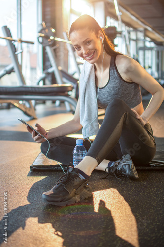 Fit girl with earphones listening to music via smartphone and resting after sports training in gym