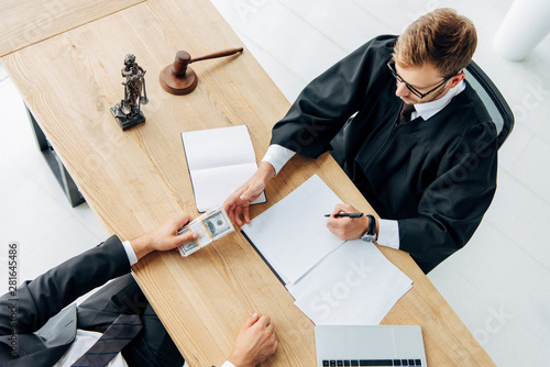 Fotografía  top view of man giving bribe to judge sitting in office