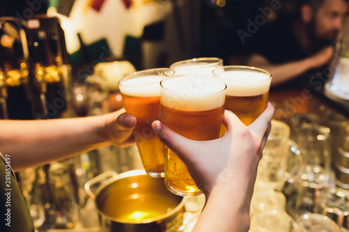Poster Pays d Asie waiter holds four glasses of beer in hands in a bar or pub. Beer glasses.