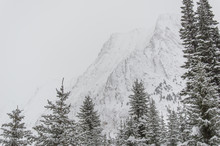 Looking Towards A Snowy Rocky Mountain Face Enduring A Blizzard