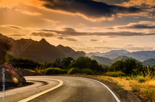 California winding highway with overcast sky, mountains background, near sunset.