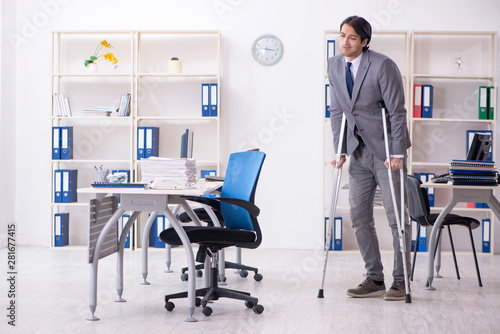 Fototapety, obrazy: Leg injured male employee working in the office