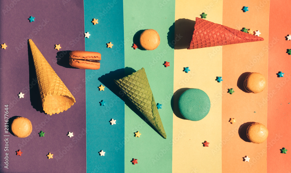 Fototapeta Sweets are scattered on a striped rainbow background: macaroons, waffle horns and small caramels in the shape of stars.