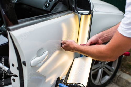 Fotografía  Repairing car dent after the accident by paintless dent repair