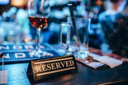 Fotografija  Plastic reserved plate on an arranged restaurant table
