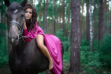 Portrait Of Young Beautiful Smiling Brunette Woman Wearing Pink Silk Dress Riding Dark Horse At Summer Green Forest.