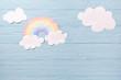 Leinwandbild Motiv Children or baby background, white clouds with rainbow on the blue wooden background