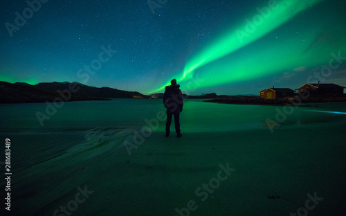 Man watching northern light dance in night sky