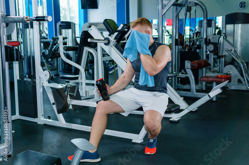 Obraz na plátně  athlete wipes his sweat between sets in weight training