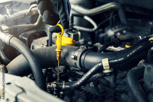 Fototapeta hand pulling out car engine oil level dip stick closeup obraz