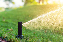 Close-up Automatic Garden Watering System With Different Sprinklers Installed Under Turf. Landscape Design With Lawn Hills And Fruit Garden Irrigated With Smart Autonomous Sprayers At Sunset Time