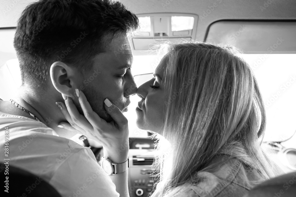 Fototapeta Couple in love man and woman kissing sitting in the car