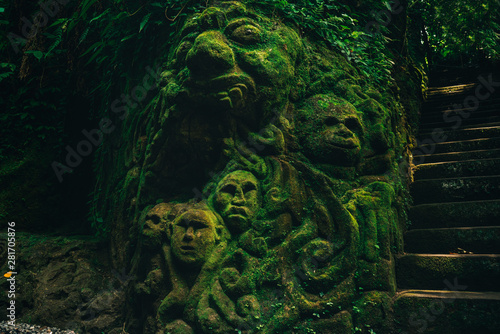 Cuadros en Lienzo Carving demons faces on wall background covered with moss texture in Bali