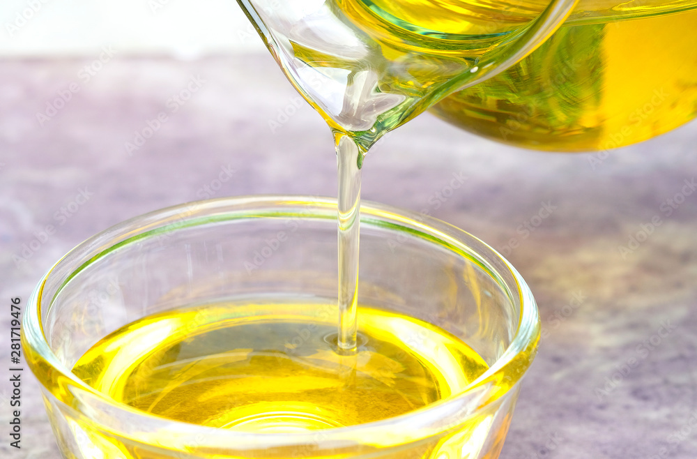 Fototapeta Pouring olive oil in the a glass bowl at stone kitchen and inside green garden view. Prepare for cooking concept. Healthcare and Beauty Concept.