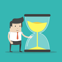 Businessman or manager looks at the hourglass. Time management concept. Flat cartoon style. Vector illustration.