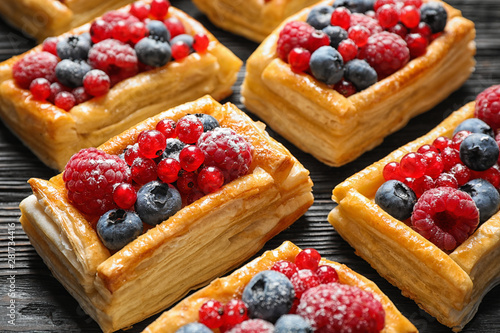 Door stickers Bread Fresh delicious puff pastry with sweet berries on dark wooden table, closeup