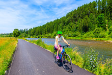 Young Woman Riding Bike On Cycling Way Along Dunajec River Near Nowy Targ, Tatra Mountains, Poland