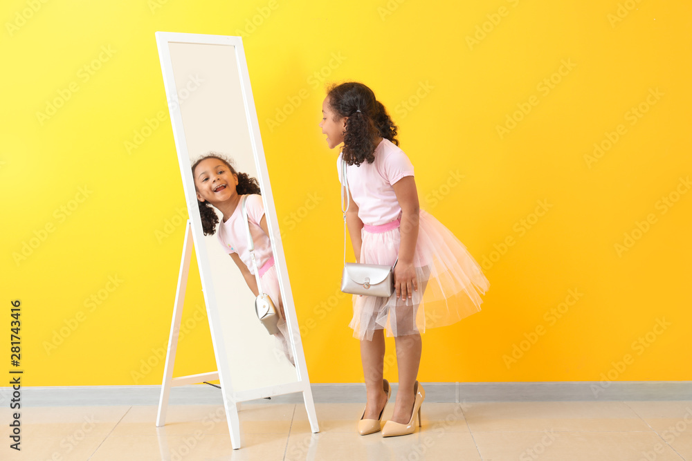 Fototapety, obrazy: Adorable little African-American girl with mother's shoes looking into mirror near color wall