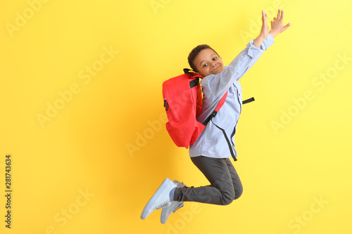 Obraz Jumping African-American schoolboy on color background - fototapety do salonu