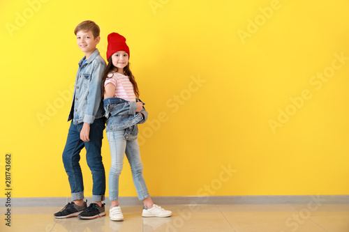Cuadros en Lienzo Stylish children in jeans clothes near color wall