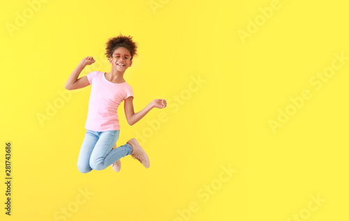 Jumping African-American girl in jeans on color background