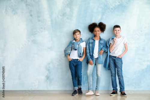 Fotografía Stylish children in jeans clothes near color wall