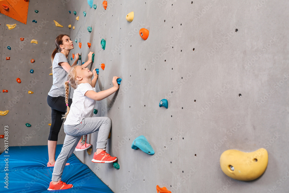 Fototapety, obrazy: Young woman with her little daughter climbing wall in gym