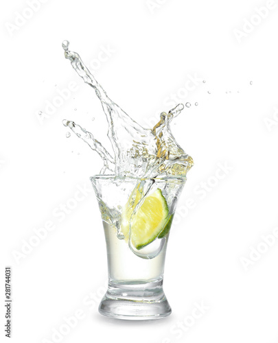 Canvas Print Dropping of lime into glass with tasty tequila on light background
