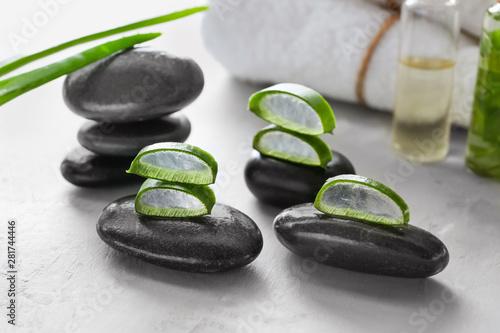 Spa stones with cut aloe vera on light background