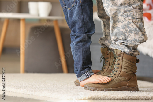 Canvastavla  Child standing of feet of his military father at home