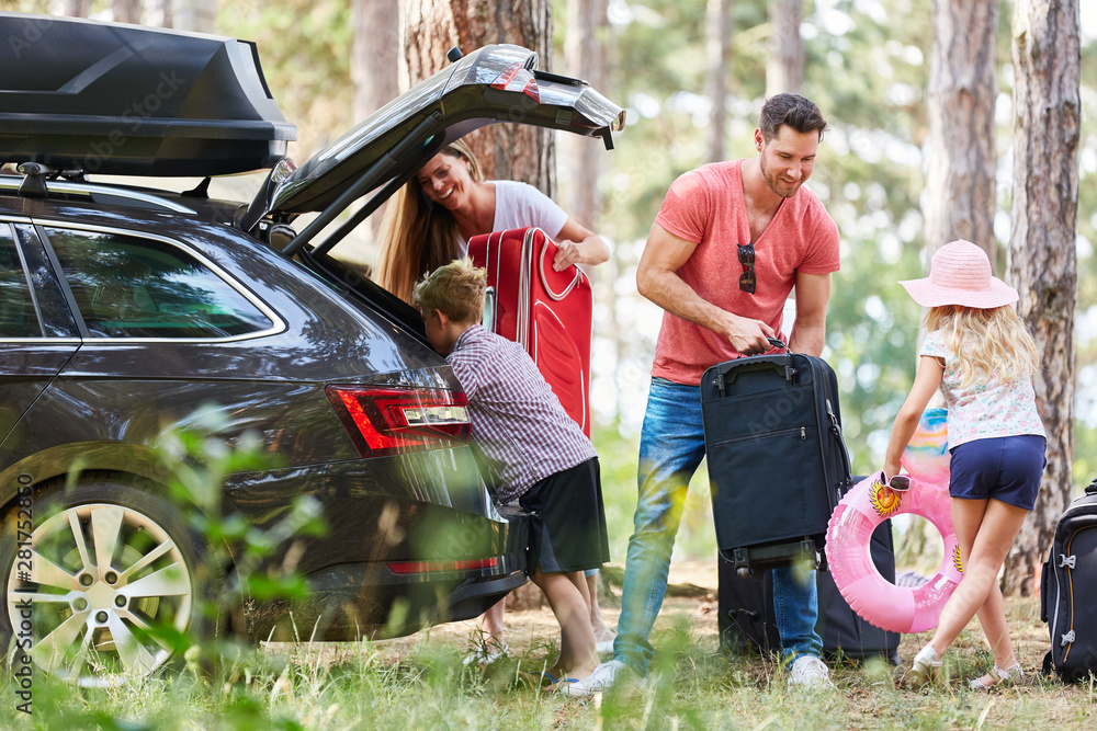 Fototapeta Kinder helfen Eltern beim Gepäck tragen