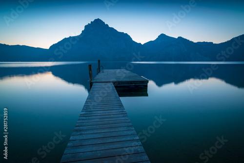 Obraz na plátně  Steg am See mit Bergen in der Dämmerung am Morgen - Traunsee in Österreich