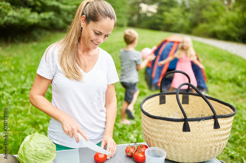 Mutter schneidet Gemüse für ein Picknick