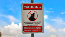Panorama Close Up Of A Warning Sign On A Neighborhood Against Cloudy Blue Sky Background
