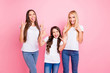 Portrait of three nice shine attractive lovely glad cheerful cheery crazy playful comic cool girls having fun showing horns symbol sign maternity isolated over pink background