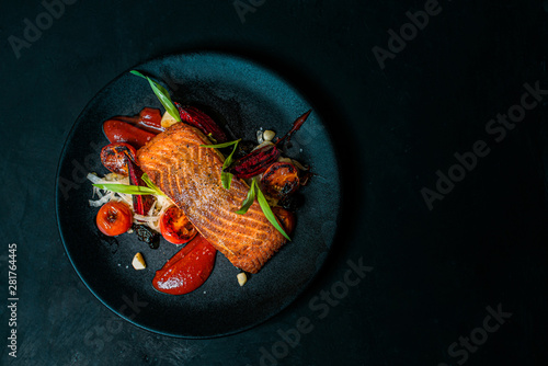 Photo  Delicious meal on a black plate, top view, copy space.