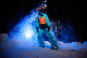 Active female snowboarder dressed in a orange and blue sportswear standing on the snow