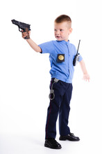 Cute Little Police Boy With Smile On Face And Gun On White Background. Intelligent Cool Children In Police Suit With Blue Eyes And Weapon