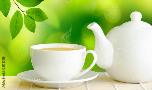 Poster Fleur Cup of green tea and white ceramic teapot on wooden table.