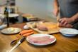 Vorbereitungen in der Küche für das Abendessen, Fischfilet und Messer im Vordergrund, Süsskartoffel schneiden unscharf im Hintergrund, Nahaufnahme