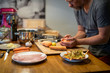 Hobbykoch nimmt mit Händen Süsskartoffel Würfel hoch, drumherum viele Zutaten, Fisch, Möhren, Knoblauch, Butter, Kochgeschirr