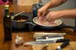 Koch legt mit der Hand Fischfilet in Pfanne am Herd, Töpfe, Ölflasche, Messer, Knoblauch, Nahaufnahme