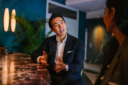 Photo  A young and attractive Chinese Asian man in a well-fitted navy suit and pocket square is talking to his companion in a meeting