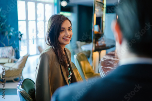 A beautiful, elegant and attractive Indian woman sits beside a young and handsome Chinese Asian man in a suit in a well-decorated interior Canvas Print